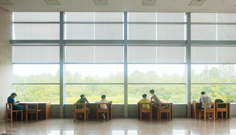 4개의 책상에 각각의 모습으로 시간을 보내는 사람들이 있으며 그 앞으로는 커다란 채광창이 있어 나무들이 잔뜩 보인다.