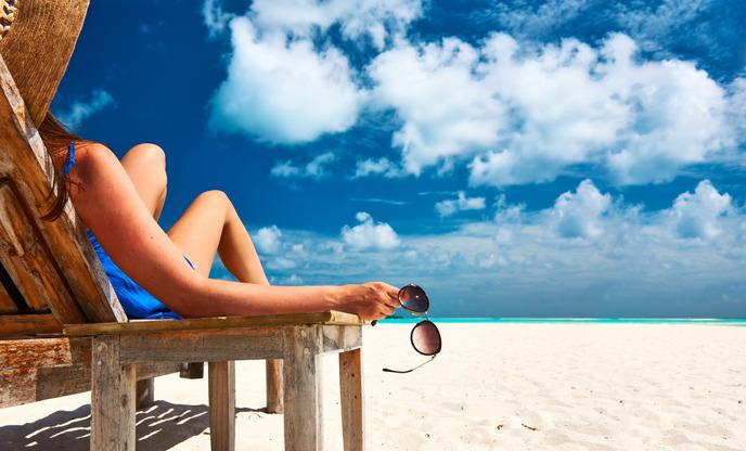 선베드에 누워서 선글라스를 들고 있는 여자 뒷모습