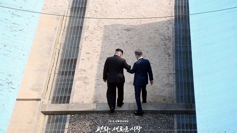 사진: 문재인 대통령과 김정은 위원장이 휴전선을 넘고 있다.